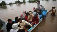 Pakistani rescue workers evacuate villagers from an area flooded by rain