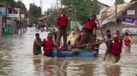 Men on a raft making their way through flood water