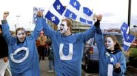 """""""Yes"""" supporters, displaying the French word """"oui"""" on their clothes, at a rally in Quebec City, Canada (29 October 1995 file picture)"""