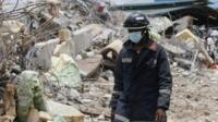 A rescue worker walks on the rubble of a collapsed building belonging to the Synagogue Church of All Nations in Lagos, Nigeria