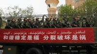 Paramilitary policemen stand on a truck as they travel past the Xinjiang International Grand Bazaar during an anti-terrorism oath-taking rally in Urumqi, Xinjiang on 23 May 2014.