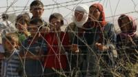 Refugees standing behind barbed wire