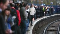 Passengers wait on platform