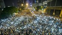 Protestors and student demonstrators hold up their cellphones during a protest outside the headquarters of Legislative Council in Hong Kong on September 29, 2014