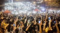 Pro-democracy protesters hold up their mobile phones as lights in front of the Hong Kong government offices on day three of the mass civil disobedience campaign Occupy Central in, Hong Kong