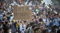 "A demonstrator hold up a sign as thousands pack the streets at a protest site on October 1, 2014 in Hong Kong. Thousands of pro-democracy supporters continue to occupy the streets surrounding Hong Kong""s Financial district"