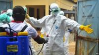 Health workers wearing protective suits prepare to carry the body of a victim of Ebola