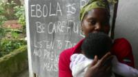 Woman and child in front of a blackboard with Ebola health
