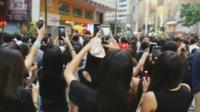 Hong Kong protesters filming sing-along with their mobile phones