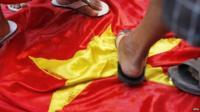 Feet standing on Vietnamese flag