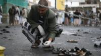 A Yemeni security official inspects the site of a suicide bombing in Sanaa, Yemen