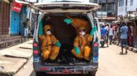 Volunteers arrive to pick up bodies of people who have died of the Ebola virus