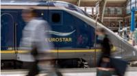 Travellers pass by an Eurostar train