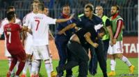 A policeman escorts a Serbian fan that invaded the pitch after a flag with Albanian national symbols was flown by a remotely operated drone during the UEFA Euro 2016 group I qualifying football match between Serbia and Albania in Belgrade on October 14, 2014