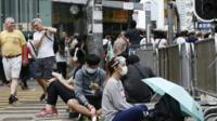 Pro-democracy protesters of the Occupy Central movement remain at an intersection as foreign nationals walk by in Mong Kok District of Hong Kong