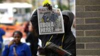 A newspaper vendor holds up a copy of the NY Post in front of the entrance to Bellevue Hospital.