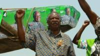 Michael Sata at a rally with his right fist raised in the air