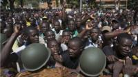 Anti-government protesters chant slogans in front of army headquarters in Ouagadougou