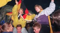 Berliner youths wave German flags during the celebration of the country's reunification at the Brandenburg Gate in Berlin 03 October 1990