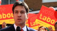 Ed Miliband campaigning in front of Labour placards