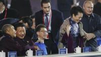 Vladimir Putin putting a coat around Peng Liyuan while seated alongside Xi Jinping and Barack Obama