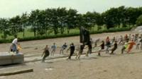 People dragging a concrete replica stone