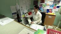 GP surgery receptionist at her desk