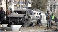 Security officials inspect the scene of a suicide car bomb attack which targeted Shukria Barakzai in Kabul, Afghanistan