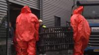 Two men in biohazard suits carrying a crate of live poultry