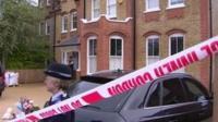 A police woman waits outside Tania Clarence's house