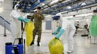 An army medic teaching National Health Service (NHS) medics how to safely dispose of potentially contaminated waste.
