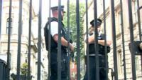 Police officers behind gate