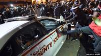 Protesters attack a police car