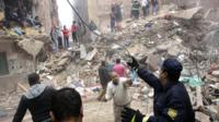 Rescue workers and volunteers search for survivors in the rubble of a building that collapsed in the Cairo suburb of Matariya
