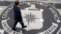 A man walks across a CIA logo