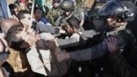 An Israeli border guard appears to grab Ziad Abu Ein at a protest near the West Bank village of Turmusaya, shortly before the Palestinian minister's death (10 December 2014)