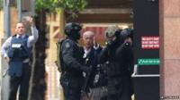 A hostage runs to safety outside the Lindt Cafe