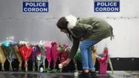 Woman places candle by police cordon