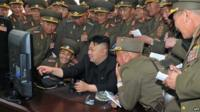 North Korean leader Kim Jong-un surrounded by military pointing at a computer screen
