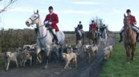 Huntsmen on horses with hounds