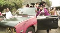 People push shabby old car