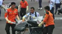 Recovery teams carrying plane wreckage