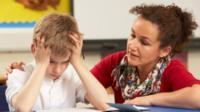 Teacher helps pupil with schoolwork