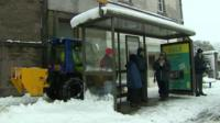 Gritter moving behind bus stop on snowy street