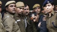 Policemen escort driver Shiv Kumar Yadav (in black jacket) who is accused of a rape outside a court in New Delhi December 8 2014