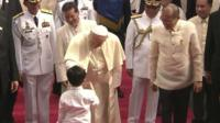 Pope Francis greets a young boy