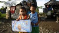 Filipino children hold a portrait of Pope Francis in village which was severely damaged by the 2013 Typhoon
