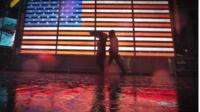 People and a US flag are reflected in puddles