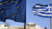 A Greek and EU flag flies in front of the ancient Parthenon temple atop the Acropolis hill