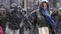 Pedestrians make their way through driving snow in midtown Manhattan in New York, Monday, Jan. 26, 2015